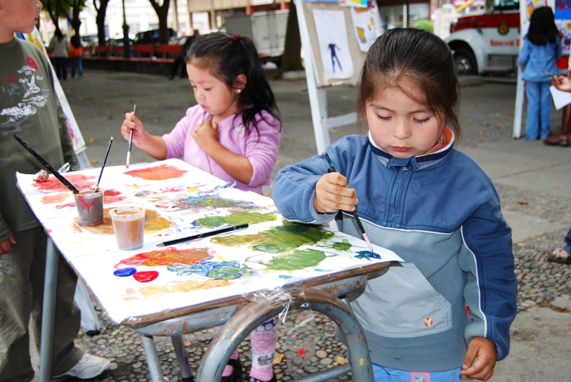 Little girls painting on white canvas using water color and brushes.