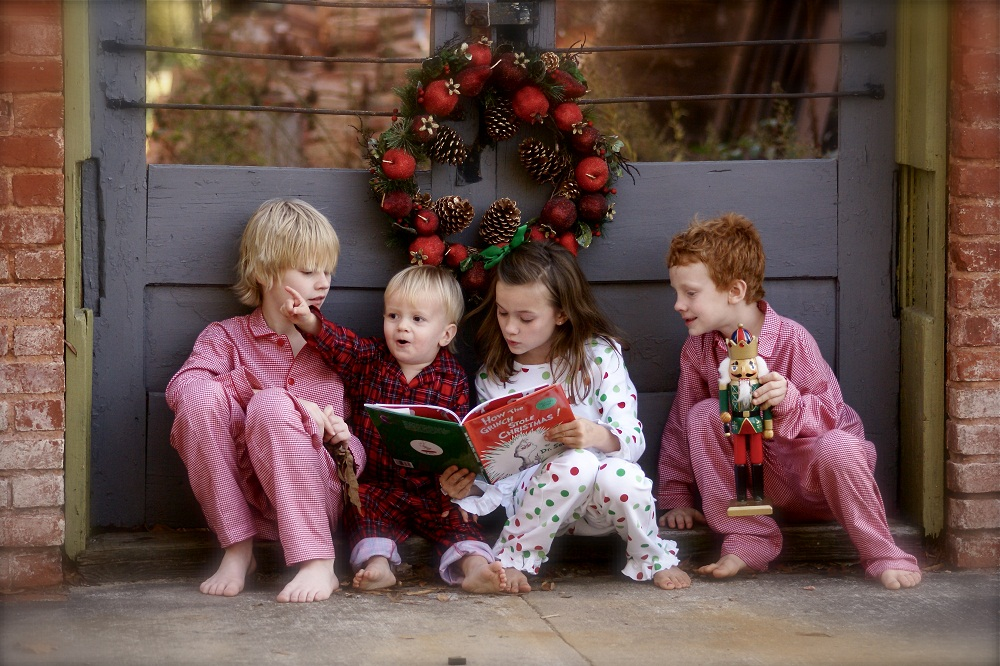Children sitting outside the door and reading How The Grinch Stole Christmas!