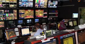 A control room with many screens