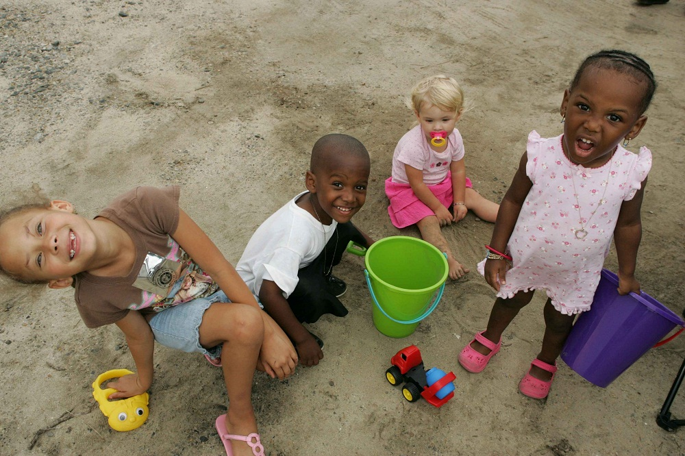 Children playing together on a sandy playground.