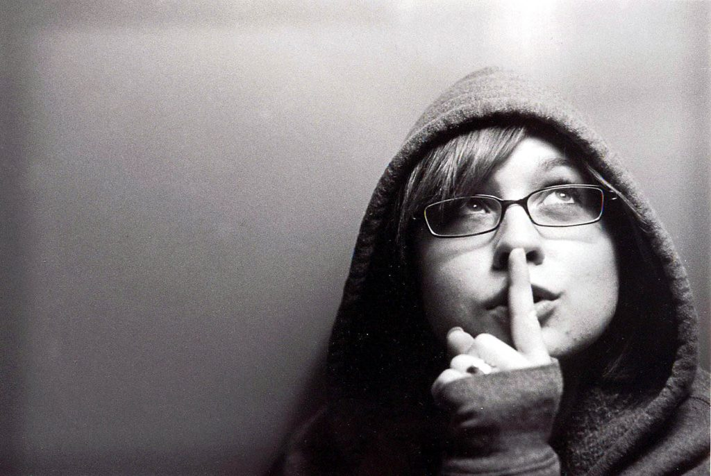 A girl is looking upward putting her finger on her lips.