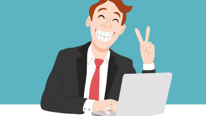A happy employee grinning and showing victory sign while using a laptop.