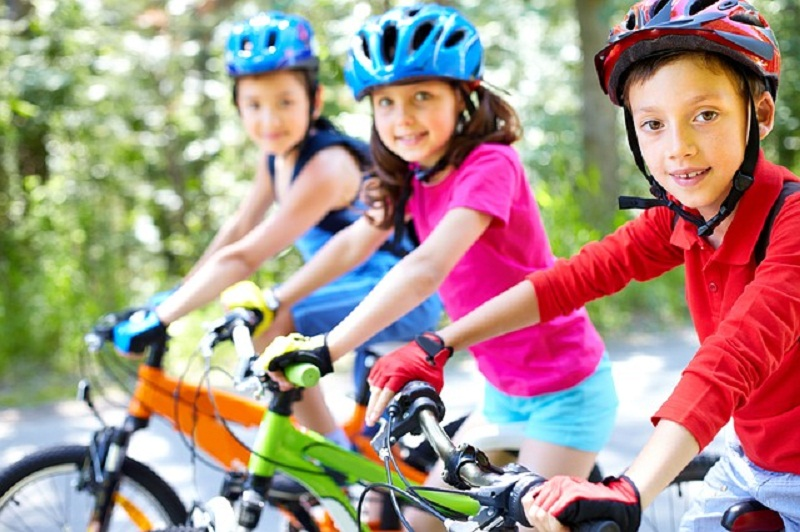 Children are riding bicycle and smiling at the camera.