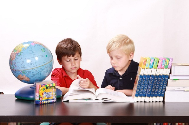 Two boys sitting at a table and reading a book. There are other books and a globe on the table.