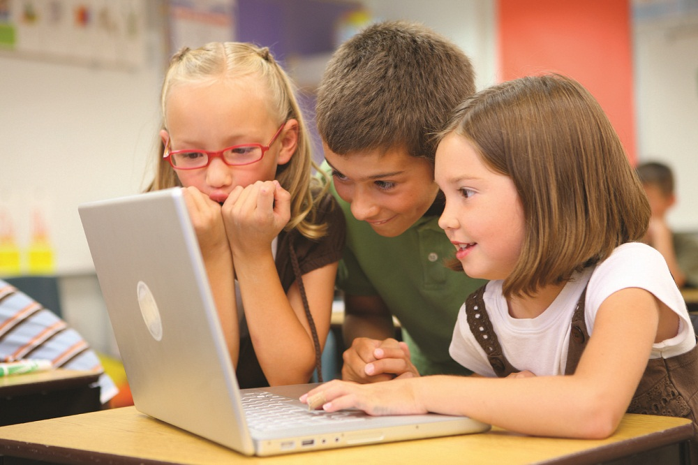 Children using laptop and smiling.