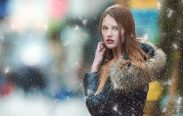 A woman wearing jacket and posing in a snowy weather.