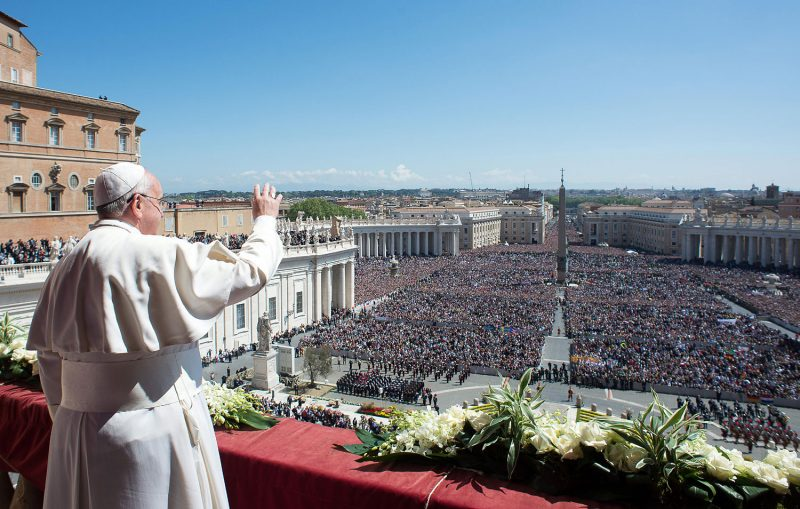 Pope Francis giving speech in front of a huge crowd.